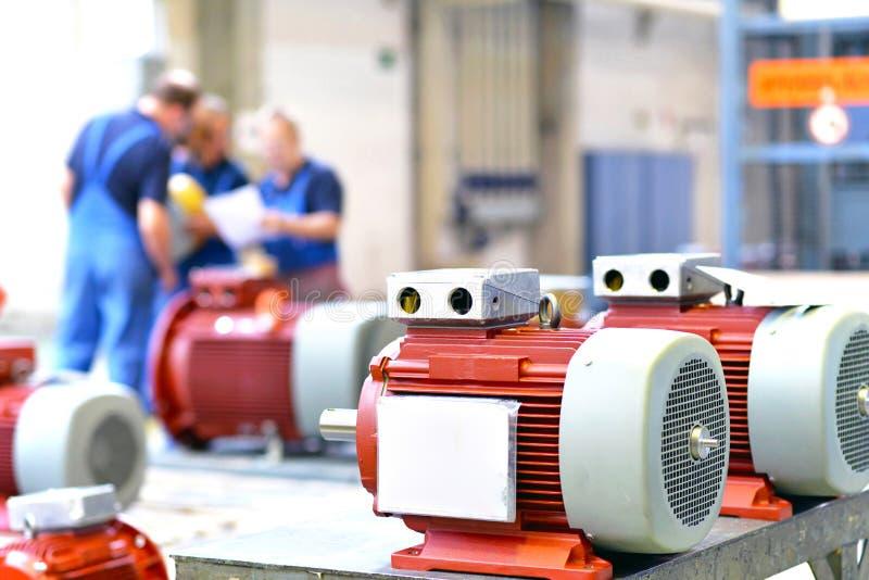 Os trabalhadores em uma fábrica montam os motores bondes imagens de stock royalty free