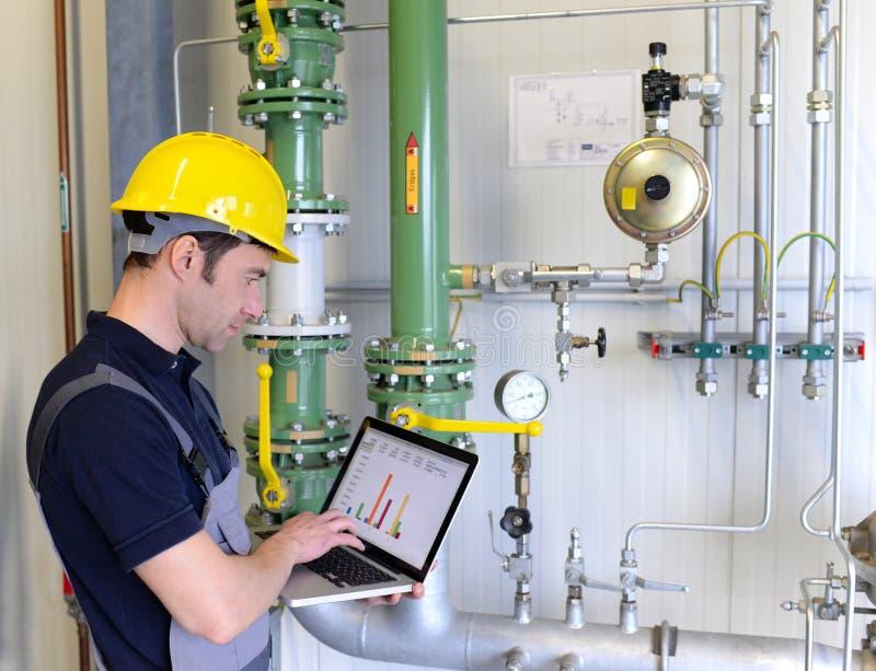 Os trabalhadores em uma planta industrial verificam os sistemas com o técnico moderno foto de stock