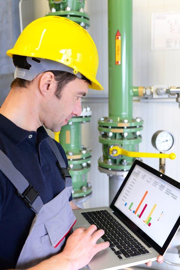 Os trabalhadores em uma planta industrial verificam os sistemas com o técnico moderno fotografia de stock