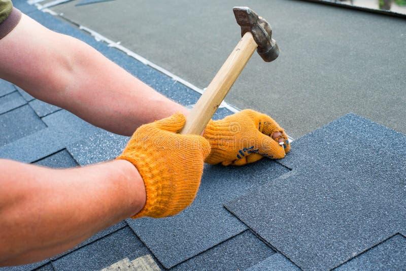 Os trabalhadores entregam a instalação de telhas do telhado do betume usando o martelo nos pregos fotografia de stock