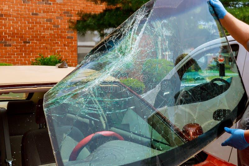 Os trabalhadores especiais quebrados do carro do para-brisa tomam do para-brisa de um carro no auto serviço imagem de stock