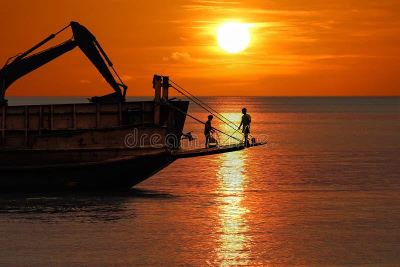 Os trabalhadores estão trabalhando para ajustar a boia de amarração na máquina escavadora da embarcação e do caminhão no oceano n fotografia de stock