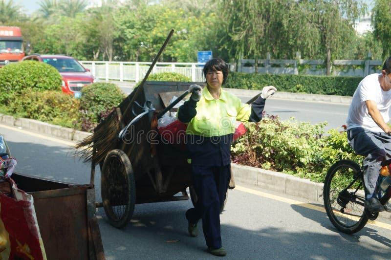 Os trabalhadores fêmeas do saneamento com um caminhão de lixo imagens de stock