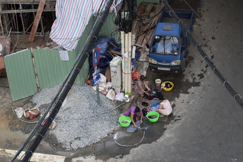 Os trabalhadores fêmeas fazem a lavanderia na rua após o trabalho do ` s do dia em um terreno de construção do condomínio em Ho C fotografia de stock