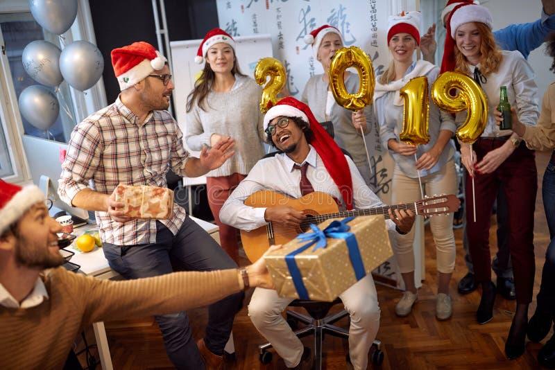 Os trabalhadores felizes do negócio têm o divertimento e a dança no chapéu de Santa em presentes da festa de Natal e da troca foto de stock