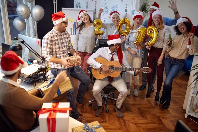 Os trabalhadores felizes do negócio têm o divertimento e a dança no chapéu de Santa no partido do Xmas junto fotografia de stock royalty free