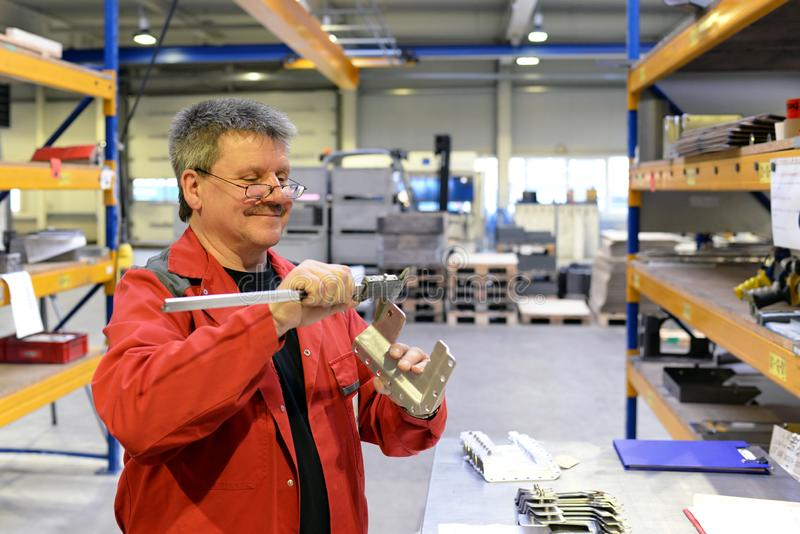 Os trabalhadores industriais inspecionam a parte do trabalho para a precisão com dispositivo de medição imagens de stock