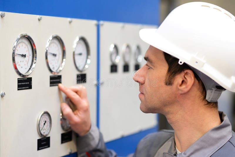 Os trabalhadores industriais leram os instrumentos de uma máquina imagens de stock