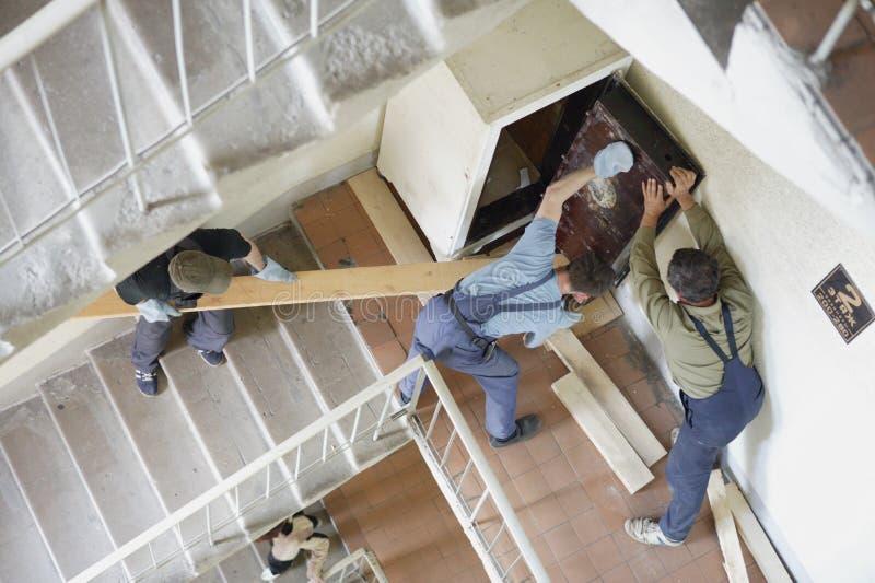 Os trabalhadores movem o cofre forte em um lstaircase foto de stock