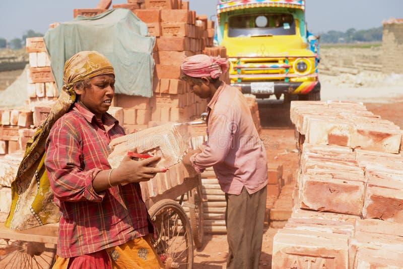 Os trabalhadores movem tijolos em uma fábrica do tijolo em Dhaka, Bangladesh Mim fotografia de stock
