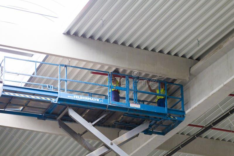 Os trabalhadores na scissor a plataforma do elevador imagem de stock royalty free