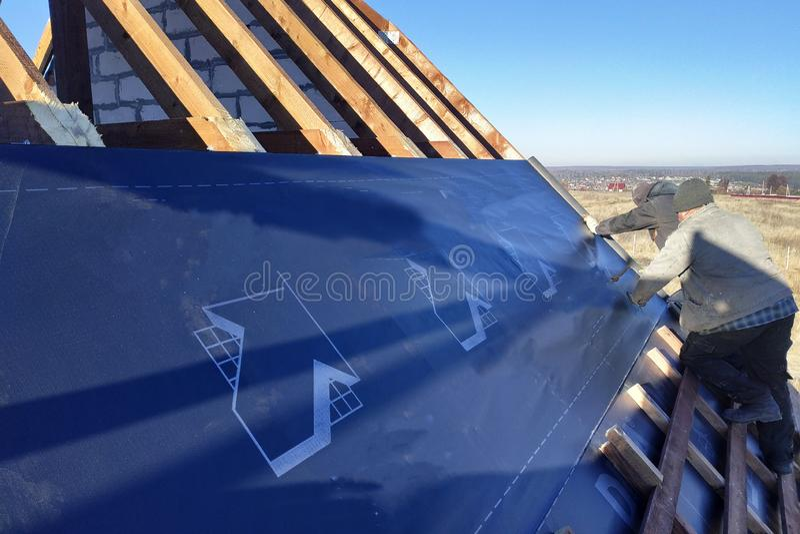 Os trabalhadores no telhado da casa instalam um filme impermeável sob o telhado e fixam-no com um grampeador fotos de stock