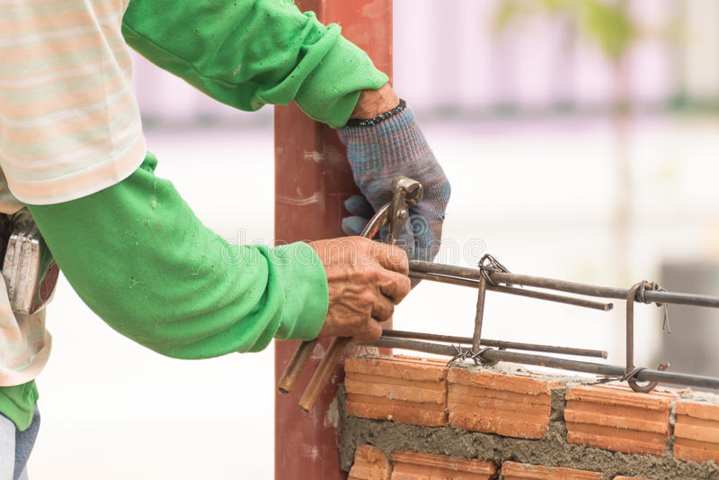 Os trabalhadores que usam o rebar do fio de aço e das quelas antes do concreto são po foto de stock royalty free