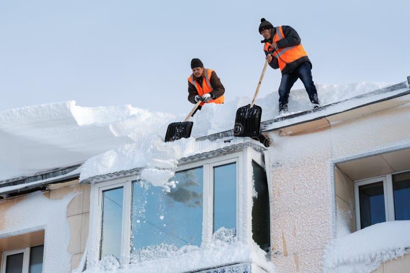 Os trabalhadores realizam a limpeza do inverno do telhado da construção da neve e do gelo após o ciclone da neve fotos de stock