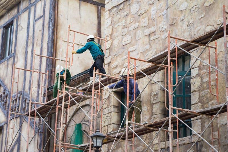Os trabalhadores sem a proteção cercam fixo no andaime no canteiro de obras foto de stock royalty free
