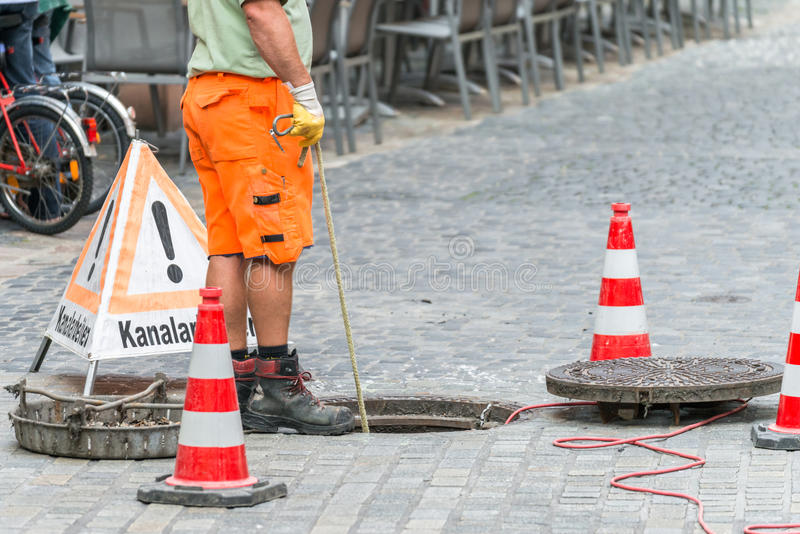 Os trabalhos da rua no canal do esgoto com advertem assinam dentro palavras alemãs para trabalhos do canal fotografia de stock royalty free