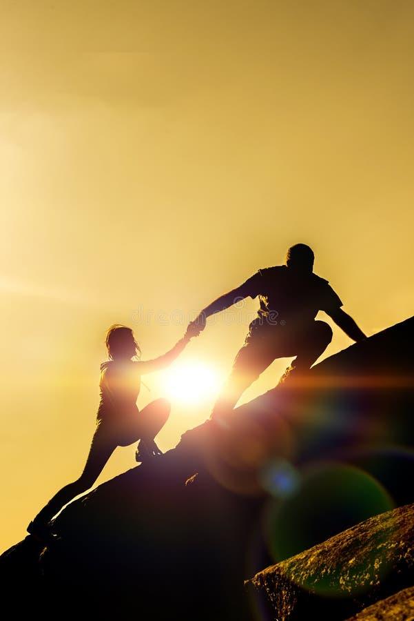 Os trabalhos de equipa comum do trabalho de viajantes do homem e da menina de dois povos ajudam-se sobre uma equipe do alpinismo imagem de stock royalty free