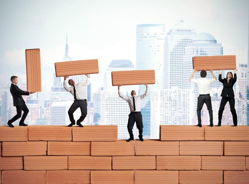 Os trabalhos de equipa constroem um negócio novo imagem de stock royalty free