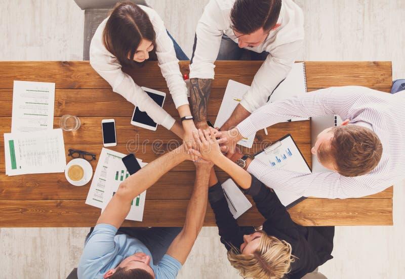 Os trabalhos de equipa e o conceito teambuilding no escritório, pessoa conectam as mãos imagem de stock