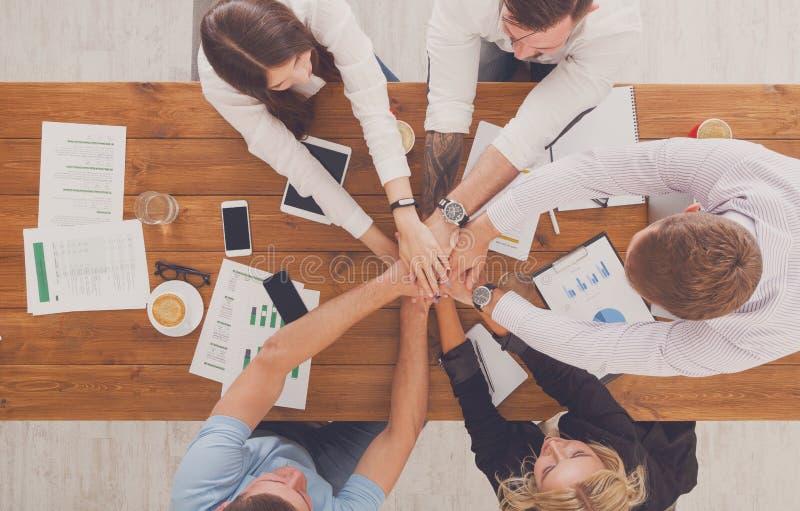 Os trabalhos de equipa e o conceito teambuilding no escritório, pessoa conectam a mão imagens de stock royalty free