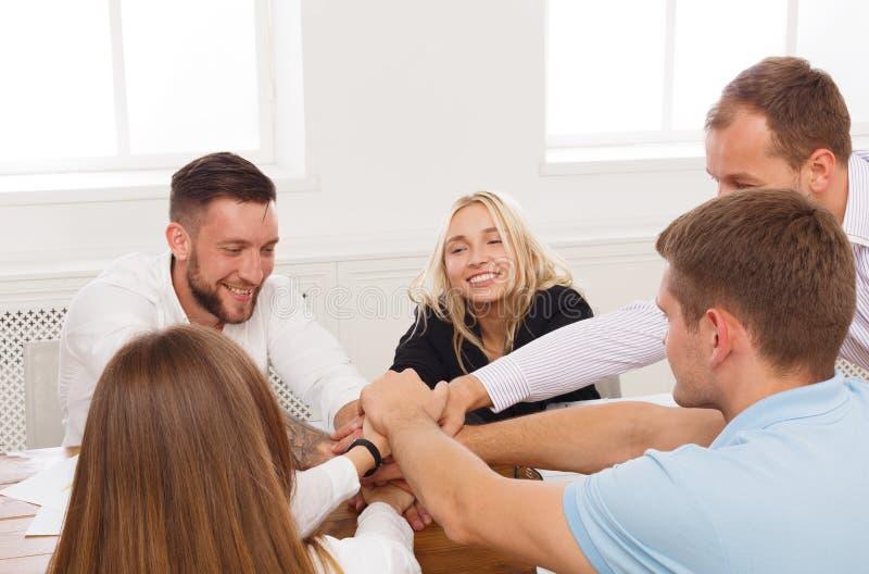 Os trabalhos de equipa e o conceito teambuilding no escritório, pessoa conectam a mão fotografia de stock royalty free