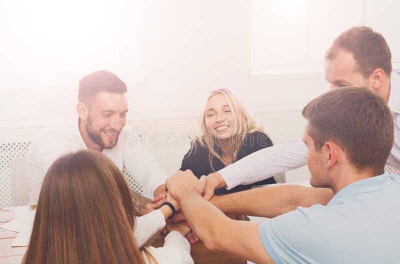 Os trabalhos de equipa e o conceito teambuilding no escritório, pessoa conectam a mão fotos de stock royalty free