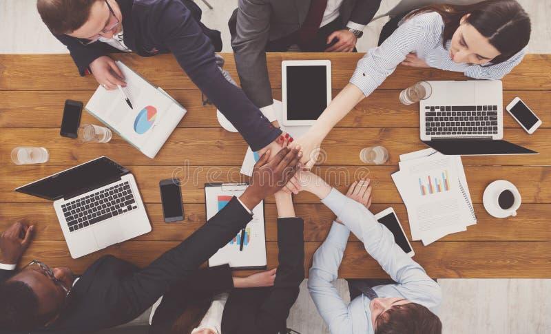 Os trabalhos de equipa e o conceito teambuilding no escritório, pessoa conectam a mão imagem de stock royalty free