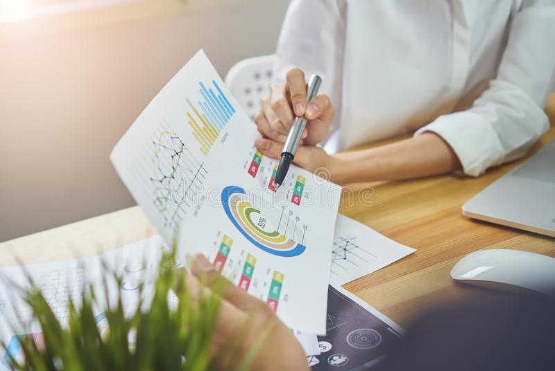 Os trabalhos de equipa estão analisando estratégias do trabalho Para encontrar a melhor maneira de crescer uma empresa imagem de stock