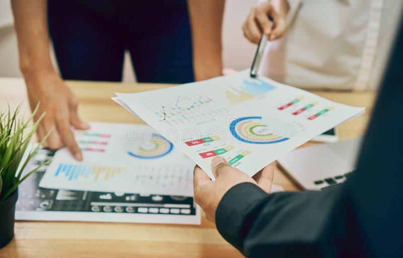 Os trabalhos de equipa estão analisando estratégias do trabalho Para encontrar a melhor maneira de crescer uma empresa imagem de stock royalty free