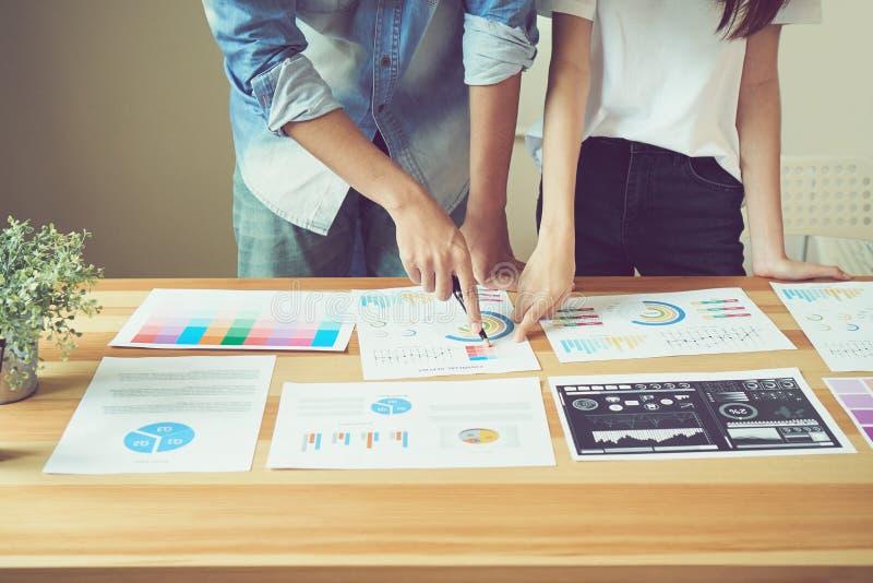 Os trabalhos de equipa estão analisando estratégias do trabalho Para encontrar a melhor maneira de crescer uma empresa fotos de stock royalty free