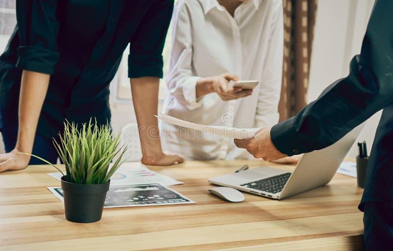 Os trabalhos de equipa estão analisando estratégias do trabalho Para encontrar a melhor maneira de crescer uma empresa imagens de stock royalty free