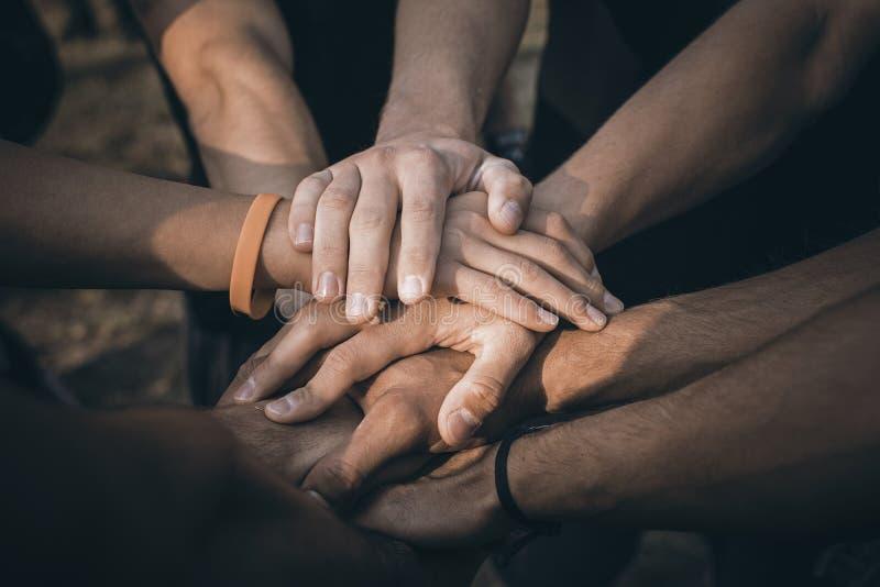 Os trabalhos de equipa juntam-se ao conceito do apoio das mãos junto Mãos de junta dos povos dos esportes imagens de stock royalty free