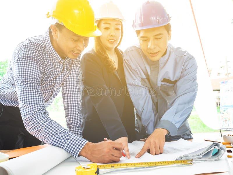 Os trabalhos de equipe do coordenador profissional estão discutindo o plano da construção do projeto com seu cliente do negócio imagem de stock royalty free