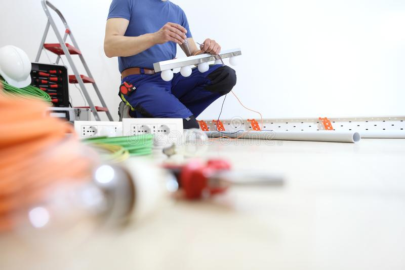 Os trabalhos do eletricista com a chave de fenda instalam as lâmpadas, circuitos elétricos da casa, fiação elétrica imagem de stock royalty free