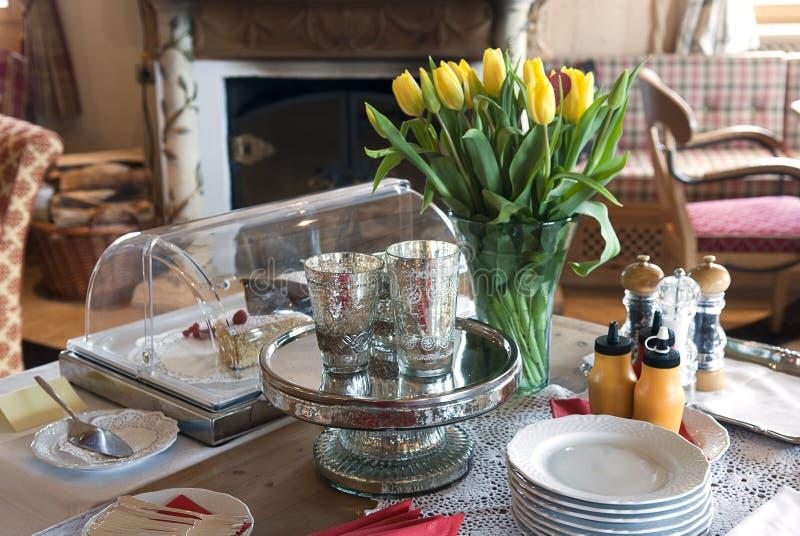 Os tulips amarelos da cutelaria em um vaso tomam o pequeno almoço no h foto de stock