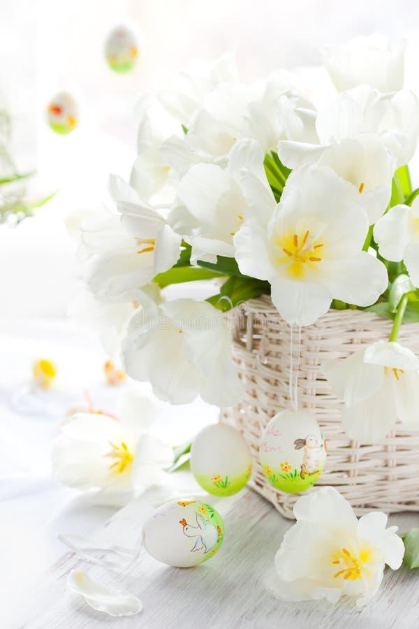Os tulips brancos em uma cesta e em um easter coloriram ovos foto de stock