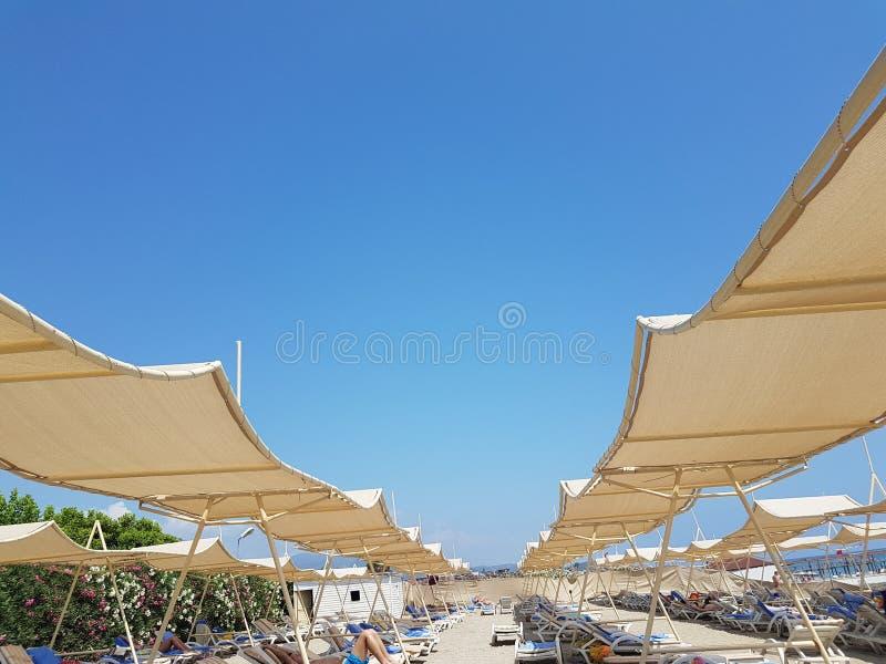Os turcos lixam com as cadeiras do guarda-chuva de sol e do sol, os povos que se estão bronzeando foto de stock