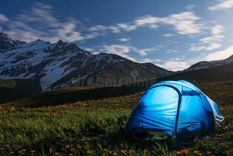 Os turistas acampam nas montanhas na noite Barraca dos caminhantes no vale da montanha da noite imagem de stock
