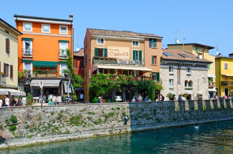Os turistas andam ao longo da rua no centro histórico de Sirmione na costa do lago Garda, Itália fotografia de stock