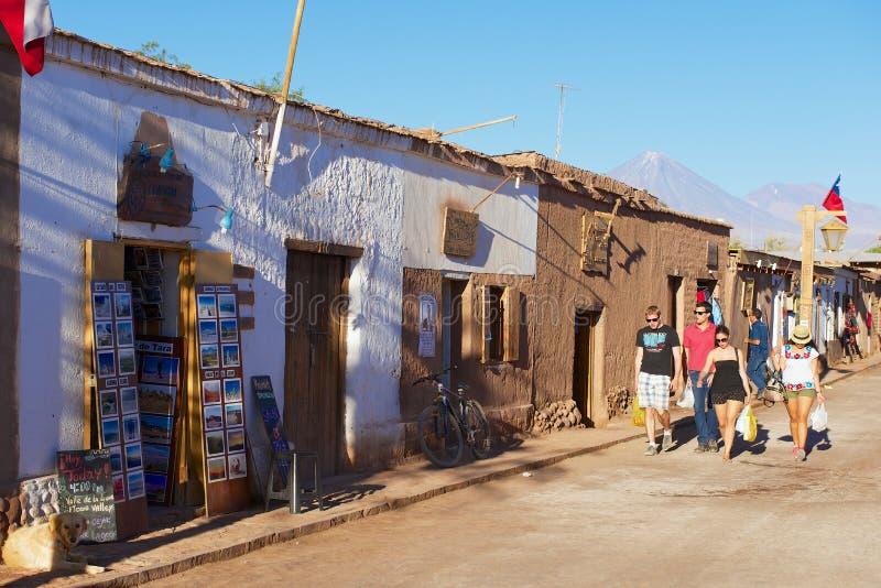 Os turistas andam pela rua da cidade de San Pedro de Atacama, o Chile imagem de stock royalty free