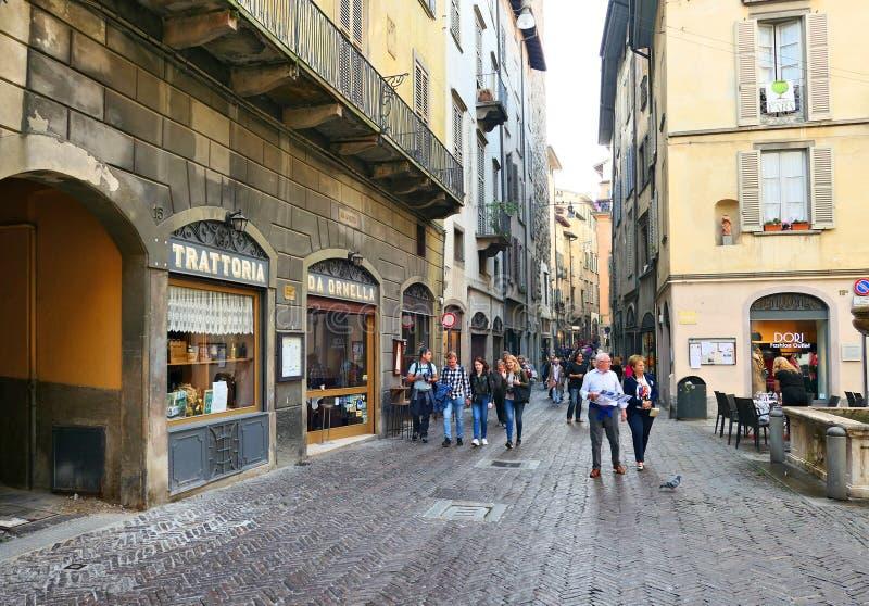 Os turistas andam a rua da cidade velha italiana de Bergamo imagem de stock royalty free