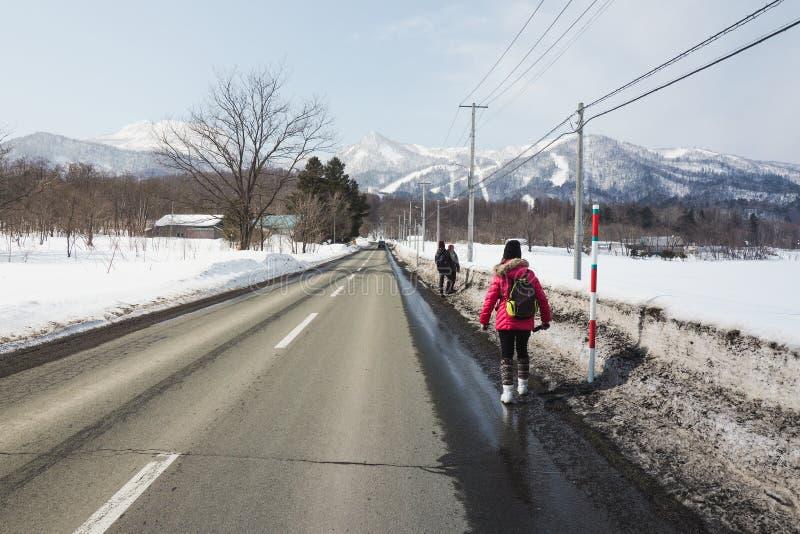 Os turistas andaram ao longo da estrada à parte superior da cidade Hokkaido de Furano porque não há nenhum serviço dos ônibus e d fotografia de stock