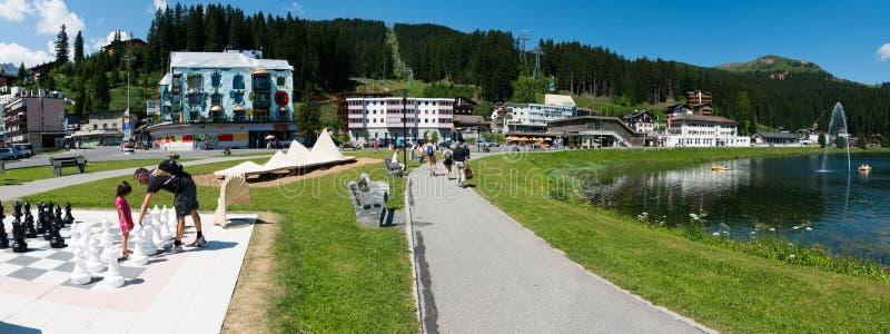 Os turistas apreciam atividades do verão no lakeshore em Arosa com a estação de trem do trem e do cabo no fundo fotografia de stock royalty free