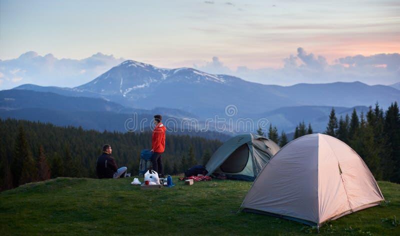 Os turistas aproximam duas barracas nas montanhas imagens de stock royalty free