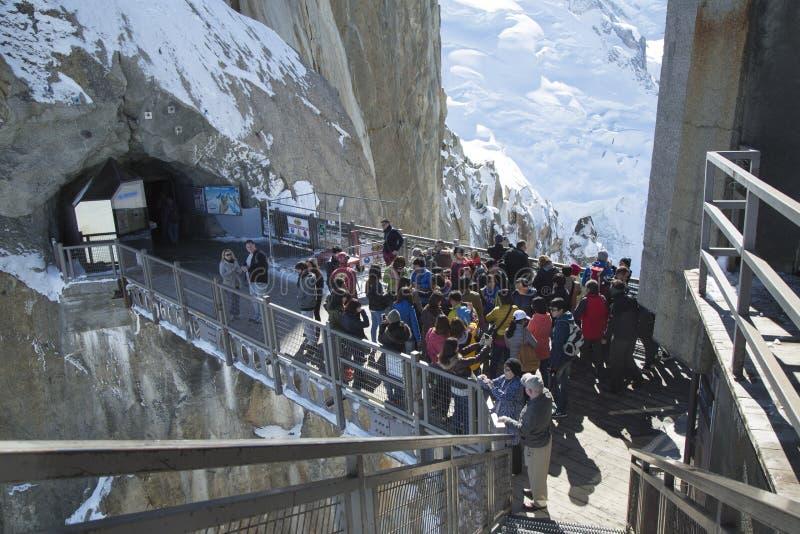 Os turistas chegaram pelo teleférico no passadiço central em Aiguille du Midi imagem de stock