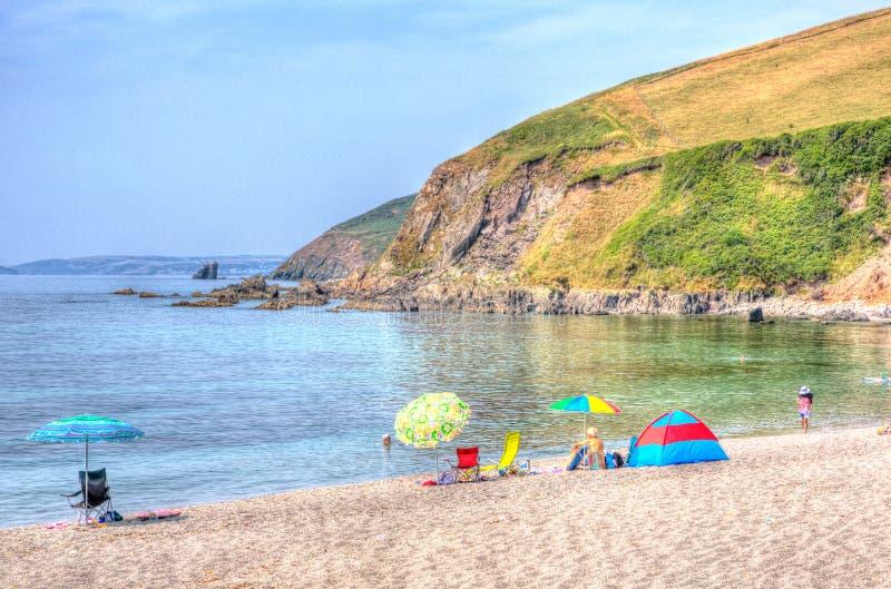 Os turistas coloriram a baía Cornualha Inglaterra Reino Unido de Whitsand da praia de Portwrinkle dos guarda-chuvas em HDR colori fotos de stock
