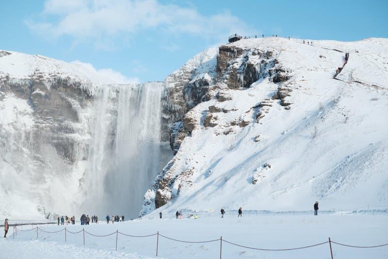 Os turistas dentro à cachoeira Skogafoss de Islândia na opinião islandêsa da paisagem da natureza na estação do inverno, o Skogaf imagens de stock royalty free