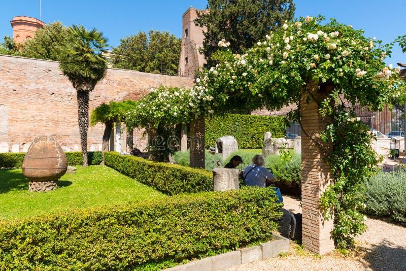 Os turistas descansam em um jardim bonito nas ruínas dos banhos de fotografia de stock royalty free