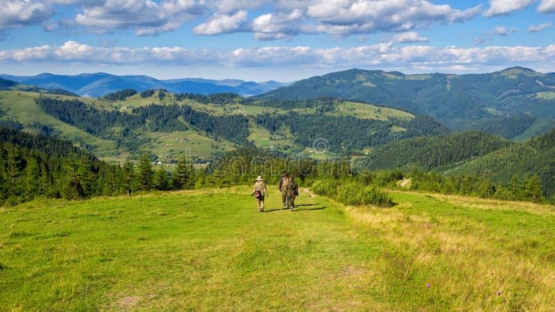 Os turistas descem das montanhas ao vale, Carpathians, Ucrânia, paisagem da natureza imagens de stock royalty free