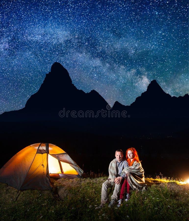 Os turistas dos pares do Sweety cobertos com uma manta que senta-se junto perto da fogueira e brilham a barraca na noite foto de stock royalty free